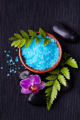 miska z solą do kąpieli pachnącą lawendą, kwiatem orchidei i kamieniami do masażu pokrytymi kroplami wody na czarnym tle.