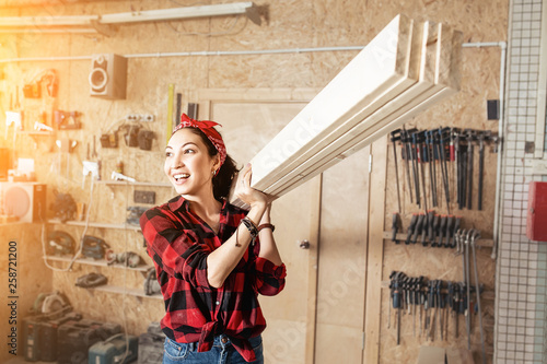Fotografering Asian woman worker carrying a wooden boards at the shoulder, the concept of blue
