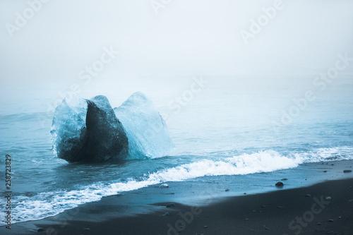 Fotografie, Obraz  Blue ice on the black volcanic beach