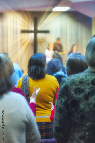 Christian congregation worship God together, with cross with light rays in backg Wallpaper Mural