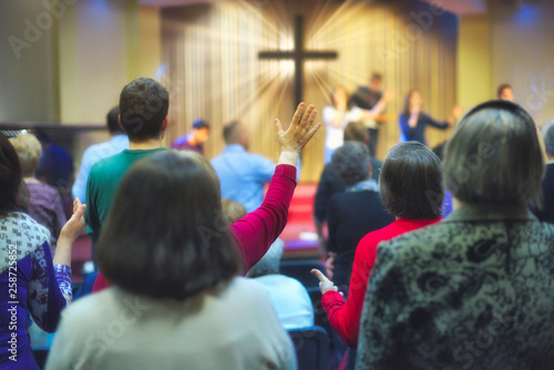 Fotografía Christian congregation worship God together, with cross with light rays in backg