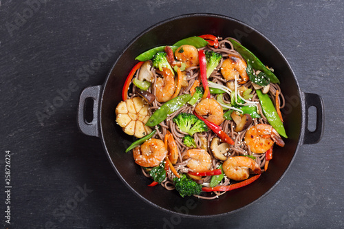 Photo  Stir fried noodles with shrimps and vegetables in a wok, top view