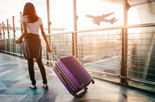 Young Woman Pulling Suitcase In  Airport Terminal. Copy Space
