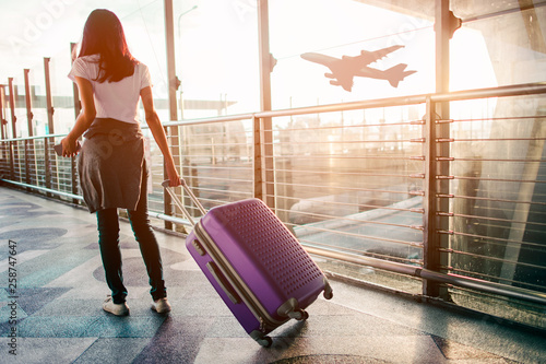 Fotografia Young woman pulling suitcase in  airport terminal. Copy space