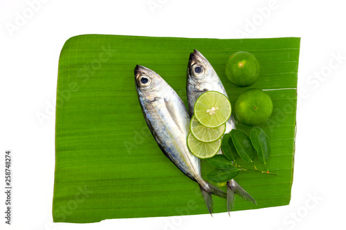 Vászonkép fish with lemon and leafs on banana leaves background
