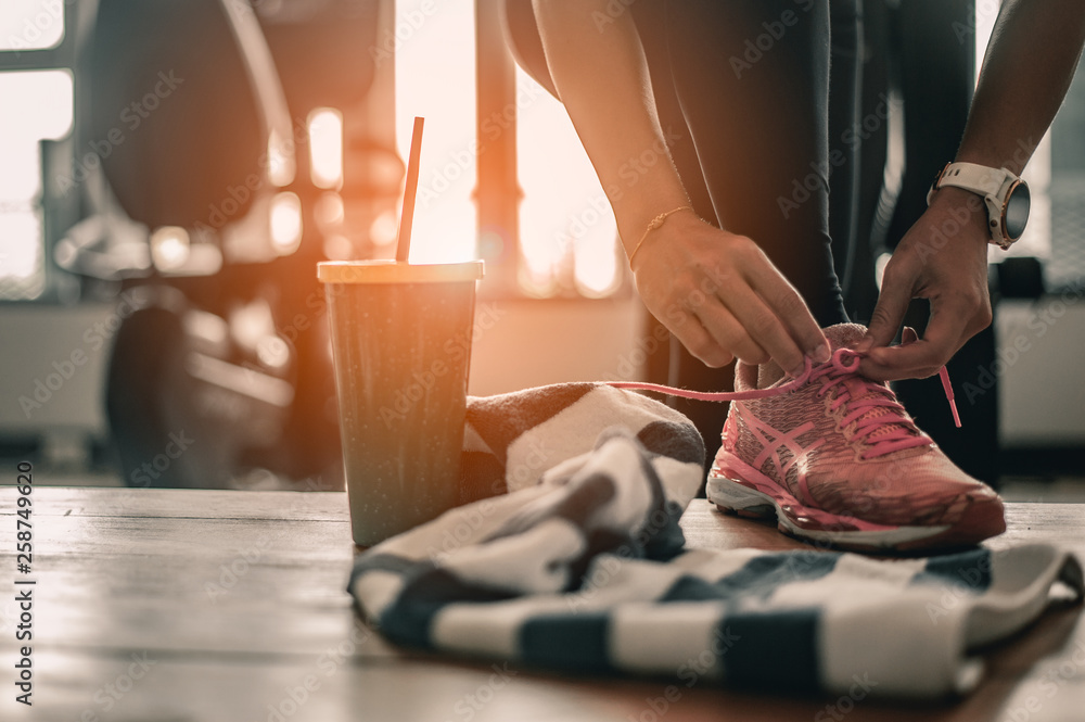 Fototapety, obrazy: woman lacing running shoes before workout. Fitness and healthy lifestyle concept.