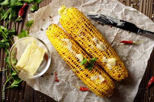 Fotomural  Top view of kitchen table with grilled sweet corn cob under melting butter and g
