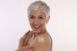 Leinwandbild Motiv Skin care,self love, Anti-aging . Mature woman applying moisturizing cream, hugging herself . Sun protection
