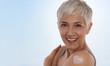 Leinwandbild Motiv Happy Smiling Mature Woman applying moisturizing Cream. Senior Skin care, beauty ,Sun protection concept