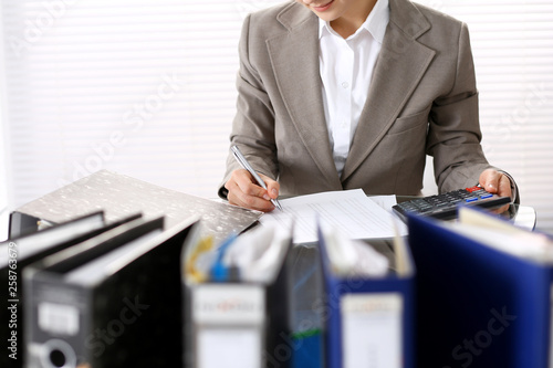 Fototapety, obrazy: Unknown bookkeeper woman or financial inspector  making report, calculating or checking balance, close-up. Business portrait. Audit or tax concepts