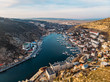 Aerial view of Balaklava landscape with boats and sea in marina bay and small town. Drone top view shot of port for luxury yachts, boats and sailboats