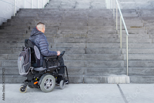 Fotografie, Obraz  Disabled man on an electric wheelchair who can't get up the stairs