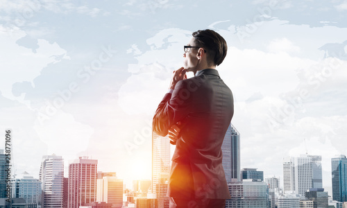 Fotografía  Concept of business success and control with confident boss against cityscape ba