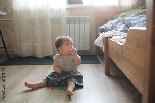 Fototapeta Little plump girl baby 10 months sitting on floor obraz na płótnie