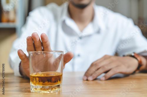 Vászonkép  Stop drunk. Person push the glass of alcohol off.