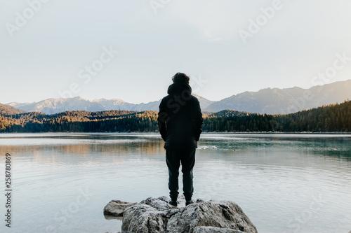 Person von hinten genießt Freiheit am See mit Ausblick auf Berge und die Natur b Canvas Print