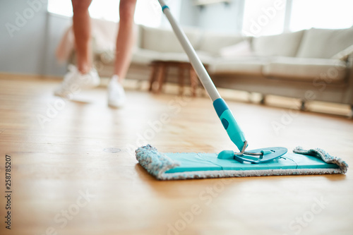 Obraz Close-up of unrecognizable woman using mop with microfiber pad while cleaning parquet floor in living room - fototapety do salonu
