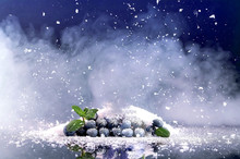 Blueberries On Background Of Snow And Smoke.