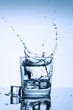 Frozen splashes of clean, spring water, in a glass with ice, on a white background.