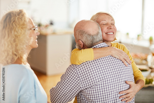 Fotografia Cheerful excited mature woman with pretty smile keeping eyes closed and hugging