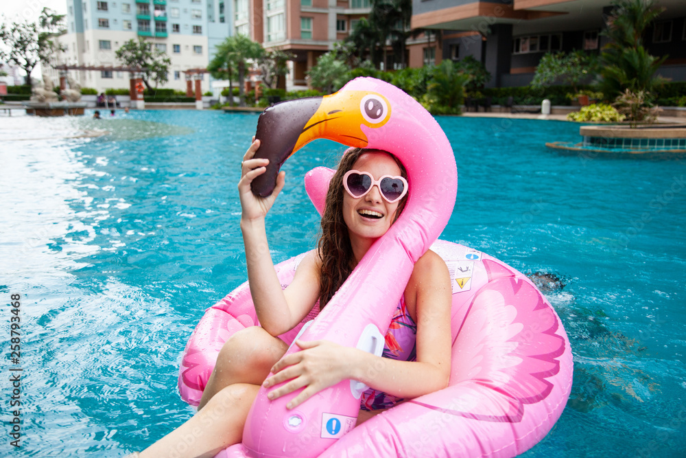 Fototapety, obrazy: Sexy girl sunglasses having fun in the pool floating on a large inflatable pink flamingo in a hotel on summer vacation