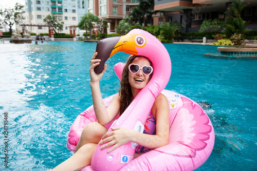 Sexy girl sunglasses having fun in the pool floating on a large inflatable pink flamingo in a hotel on summer vacation