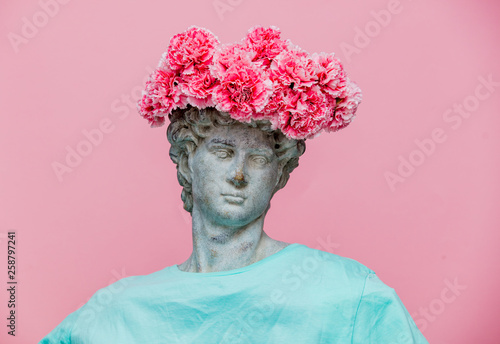 Foto  Antique bust of male with carnations bouquet in a hat