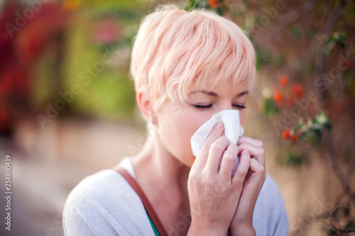 Valokuva  Woman with with allergy symptom blowing nose