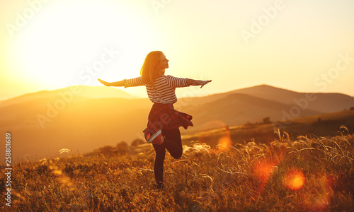 Photo  Happy woman jumping and enjoying life  at sunset in mountains.