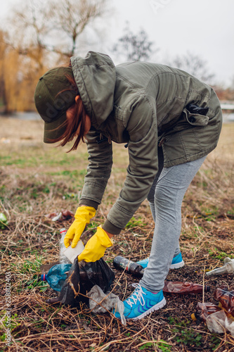 Woman volunteer cleaning up the trash in park  Picking up