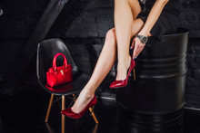 Beautiful Legs Woman Wearing Black Dress With Red Purse Hand Bag With High Heels Shoes Sitting On The Black Bench. Lifestyle!