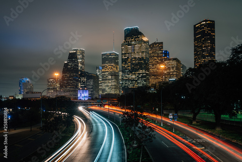 Fototapeta Long exposure of traffic on Allen Parkway and the Houston skyline at night, in H