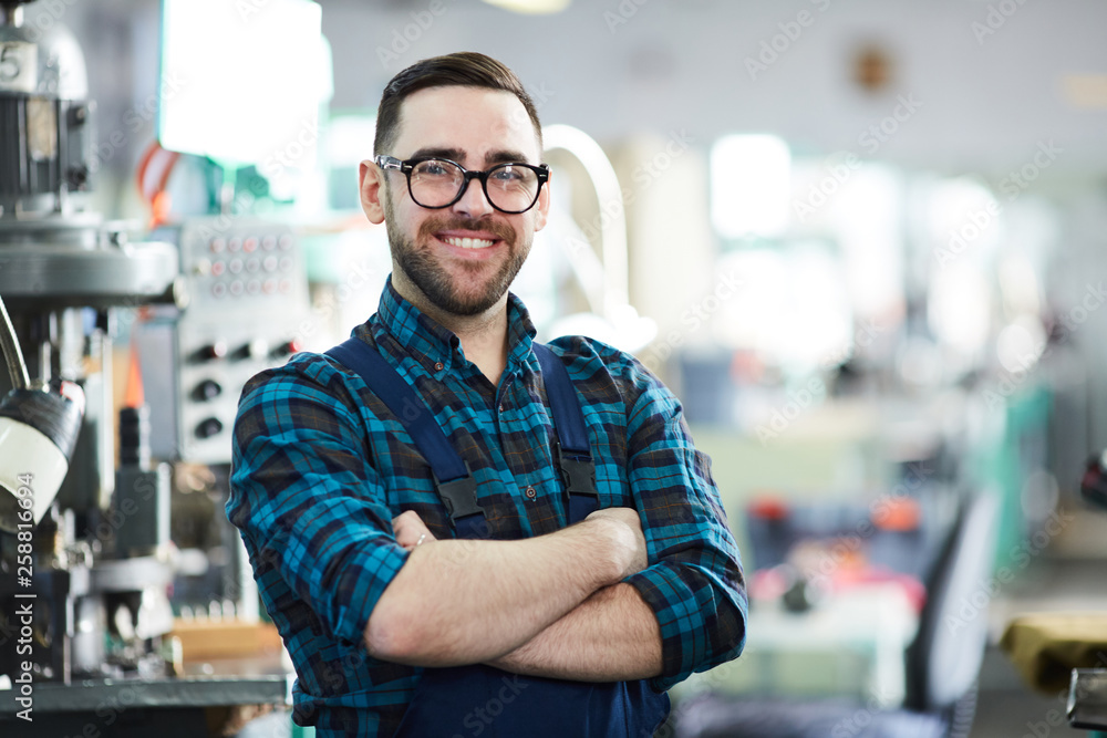 Fototapeta Waist up portrait of cheerful factory worker looking at camera while posing in workshop standing with arms crossed