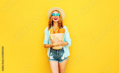 Fotografering  portrait happy laughing young woman holding paper bag with long white bread bagu