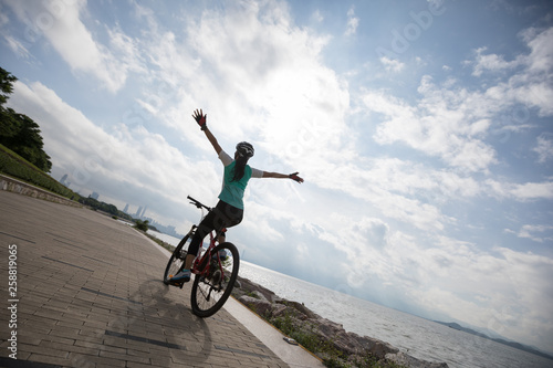 Hands free cycling woman riding Mountain Bike on sunrise seaside Canvas Print