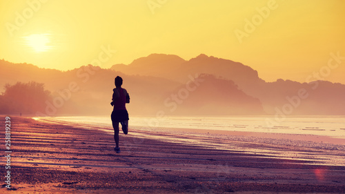Silhouette of young fitness woman running at sunrise beach фототапет