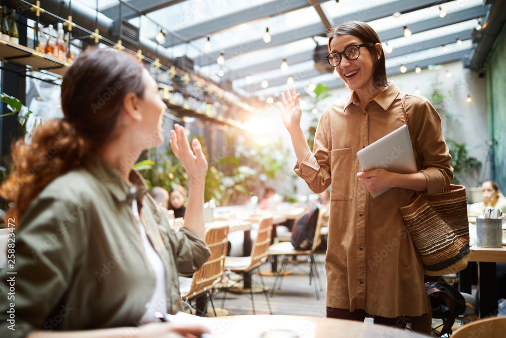 Fototapety, obrazy: Cheerful excited young women waving hands while greeting each other in cafe, they meeting by chance in public place