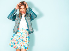 Portrait Of Young Beautiful Smiling Hipster Girl In Trendy Summer Jeans Jacket Clothes. Sexy Carefree Woman Posing Near Blue Wall. Positive Model Having Fun