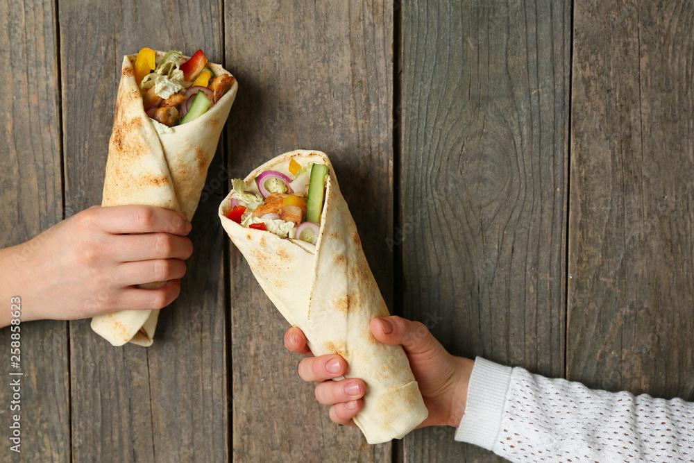 Fototapety, obrazy: Female hands with tasty doner kebab on wooden background