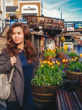 Girl With Long Hair In A Coat Walking On The Pier In San Francisco On The Background Of Yellow Tulips