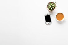 Top View Of Empty Office Desk. Green Plant In A Pot, Cup Of Coffee And Pocket Communicator Smart Phone On White Background. Copy Space For Your Text