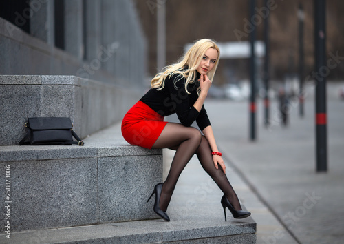 Photographie  Girl with perfect legs in pantyhose at the city square.