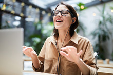 Positive Carefree Young Woman In Wired Earphones Sitting At Table And Using Laptop While Gesturing Hands And Singing Favorite Song At Workplace