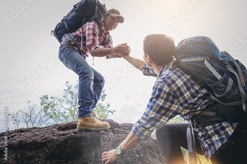 Leinwand Poster Young man with backpack helping friend to climb up to the top of mountain