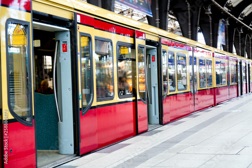Red train on railroad station with opened doors in Berlin, Germany.