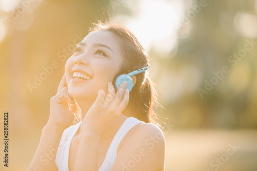 beautiful asian woman listening music in the park - 258882822