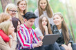A group of teenagers 15-19 years old are sitting in the summer forest with a tablet. Close-up.