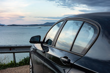 Rear View Of Modern Luxury Black Car Parked Above The Sea With A Romantic View During The Sunset