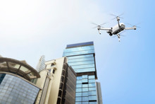 White Drone With Camera Flying To The Top Of Modern Building
