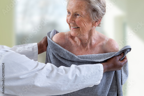 Photo Care giver or nurse assisting elderly woman for showerand drying her